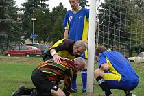 Kapitán týmu David Beneš, Gajdoš (vpravo) a rozhodčí Kodl se sklánějí nad veteránem v brance Františkem Pavlem, který schytal v Černém Dubu při utkání III. třídy hodně ran, porážce Trhových Svinů B 1:3 ale nezabránil.