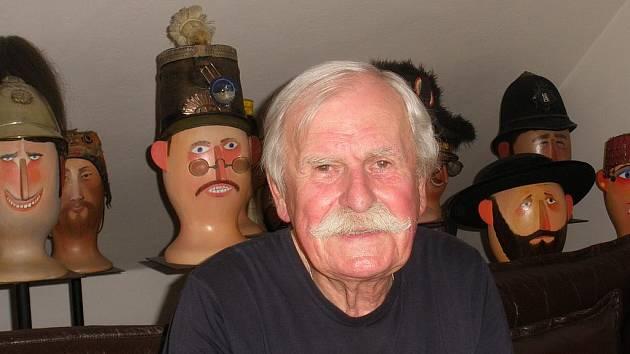 Ilustrátor Adolf Born ve svém ateliéru se sbírkou čepic.