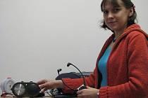 Ředitelka Poradenského centra pro neslyšící a nedoslýchavé Jana Kubínová ukazuje kompenzační pomůcky – signalizaci domovního zvonku (vlevo) a sluchátka pro poslech televize.