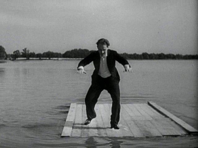 Jiří Voskovec balancuje a poskakuje na voru. Jeho kamarád Tonda je mimo kameru ve vodě.