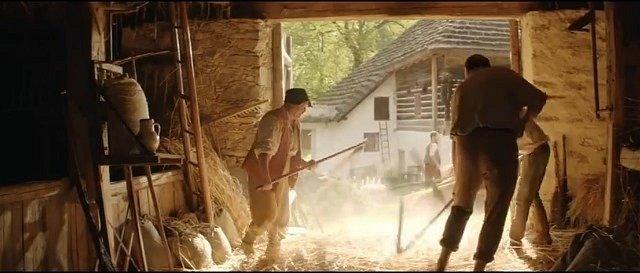 Jaroslav Janout, správce mlýna (zády vpravo) při práci s cepem. Za ním je ukrytý herec Oldřich Kaiser.