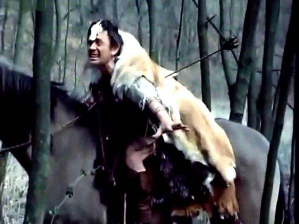 Aršun padá zkoně poté, co ho zasáhl šíp Havranpírka. Herec Karel Hlušička má na čele lebku ptáka.