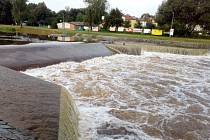 Malý jez na Malši v Českých Budějovicích při zvýšeném průtoku. Přibližně od průtoku 10 kubíků za vteřinu se pod jezem vytváří nebezpečný vodní válec. Obvyklý letní průtok je v řádu jen několika kubíků. Snímky z počátku srpna 2020.