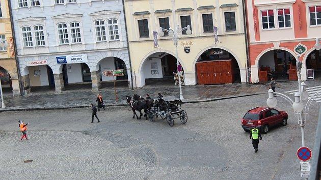 Pohřební kočár s dvěma koňmi projíždí centrem města.