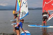 Za mírného vánku vyjíždějí surfeři na start víkendového lipenského závodu v Černé v Pošumaví.