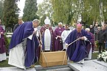 Generální vikář Adolf Pintíř (vlevo) a světící biskup Pavel Posád ukládají do hrobky ostatky Mons. Martina Josefa Říhy.