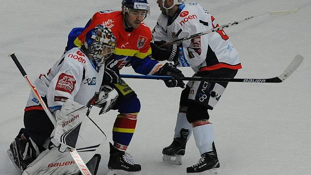 Útočník ČEZ Motoru Martin Heřman (v modrém) se prosazuje před kanadským brankářem Chomutova Justinem Petersem, kterému pomáhá Jakub Sklenář.