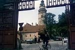 Červená brána. Říká se jí tak podle barvy nátěru. Tudy se vstupuje z Latránu na I. nádvoří českokrumlovského zámku. Na první pohled je zjevné, že v době natáčení byla brána poškozena.