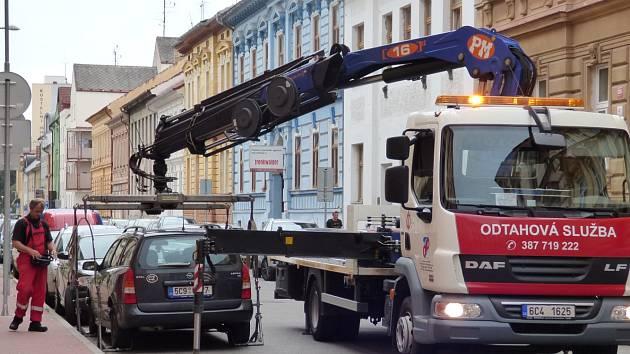 Odtahová služba nakládá osobní automobil v Kostelní ulici. Podle nového opatření totiž parkovalo na místě vyhrazeném pro zastavení autobusů.