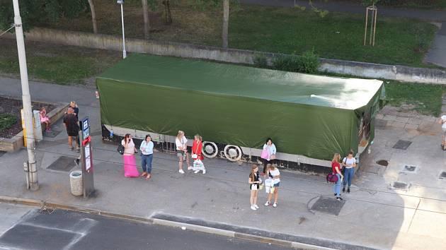Českobudějovická Pražská třída bez kovových konstrukcí, které se nacházely nad chodníkem poblíž křižovatky s Pekárenskou ulicí. Pod zelenou plachtou je aktuálně neprovozované rychlé občerstvení.