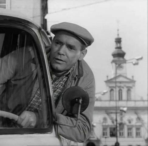 """Na českobudějovickém náměstí se vyklání z auta řidič Vosátka (Gustav Haverle).  Málem porazil Ivana, jemuž říká: """"Hvězdář a nevidí velký vůz."""""""