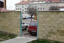 Průchod mezi parkovišti obou obchodů zatarasila mříž.