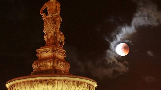 Úplné zatmění měsíce, jak je mohli pozorovat občané v Českých Budějovicích na náměstí Přemysla Otakara II, s dominantou sochy Samsona na kašně.