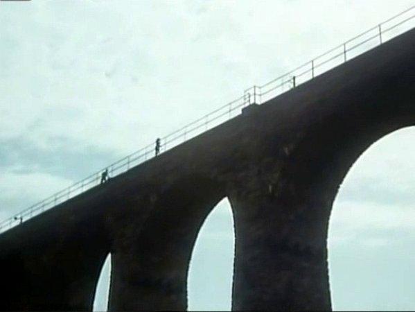 Záběrem na viadukt shorní partií a kovovým zábradlím film začíná ikončí.