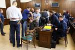 Jednání komplikuje i velký počet účastníků. Každý ze sedmi obžalovaných má svého obhájce a strážce z vězeňské služby. K tomu se musí vše tlumočit.