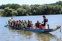 Dav lidí přihlížel v sobotu z břehu Vltavy na závodníky dračích lodí.