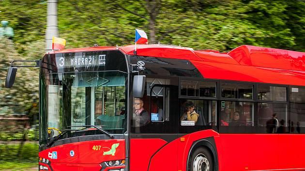 Krajským městem projíždí vozy MHD s vlajkami.