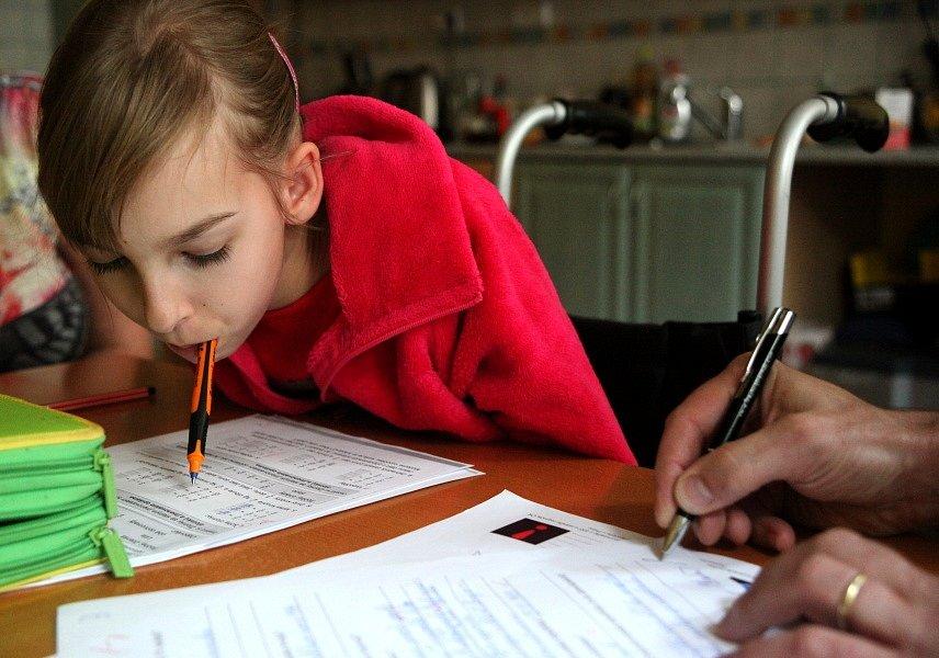 Bára píše domácí úkol z matematiky. Její táta jí ho podepisuje.