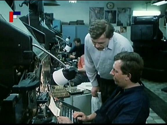 Záběr zfilmu Tichý společník, který se natáčel vČeských Budějovicích. Jiří Schmitzer se sklání nad komparzistou Václavem Rachačem, zaměstnancem tiskáren.