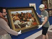 Alšova jihočeská galerie otevřela na Hluboké výstavu Ilja Repin a ruské umění. Nabízí přes 100 prací, potrvá do 27. září. Na snímku zaměstnanci galerie s dílem Ilji Repina Záporožští kozáci píší dopis tureckému sultánovi.