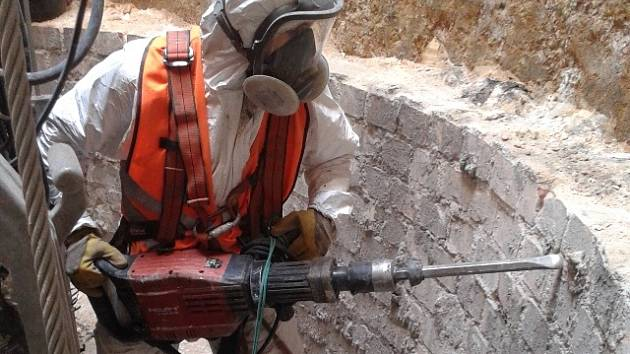 Uvnitř teplárenského komína pracují od začátku srpna dělníci se sbíječkami. Vybourat jeho vnitřek představuje těžkou ruční práci.