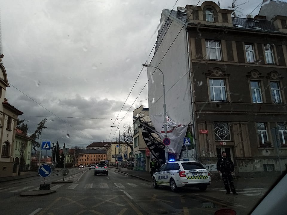 V Dukelské ulici v Českých Budějovicích u přechodu od pedagogické fakulty k Jihočeskému muzeu se utrhl billboard připevněný na stěně domu. Pomáhají ho zajistit strážníci.