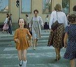Přechod pro chodce u píseckého hotelu Otava v Komenského ulici. Na snímku je vidět budova zdejšího gymnázia. Dívenka přechází po zebře tam a zpět a napodobuje panáčka, když na semaforu naskočí zelená.