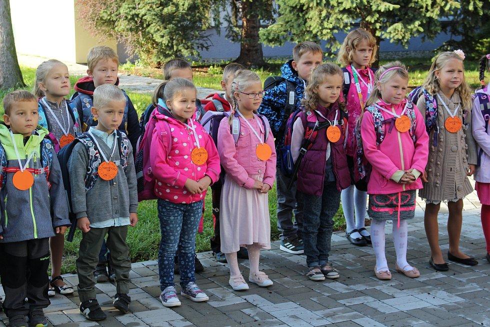Pasování prvňáčků a předávání diplomů na školním dvoře.
