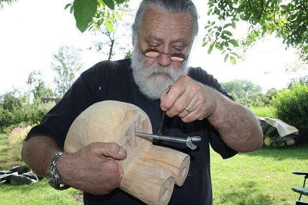 Nejdřív upevnit, , pak řezat. Do dřevěné sochy Josef Hanusch zavrtává vrutošroub, sjehož pomocí si pak dílo upevní na řezbářskou stolici, laicky ponk. To aby mohl dlátem pořádně zabrat.