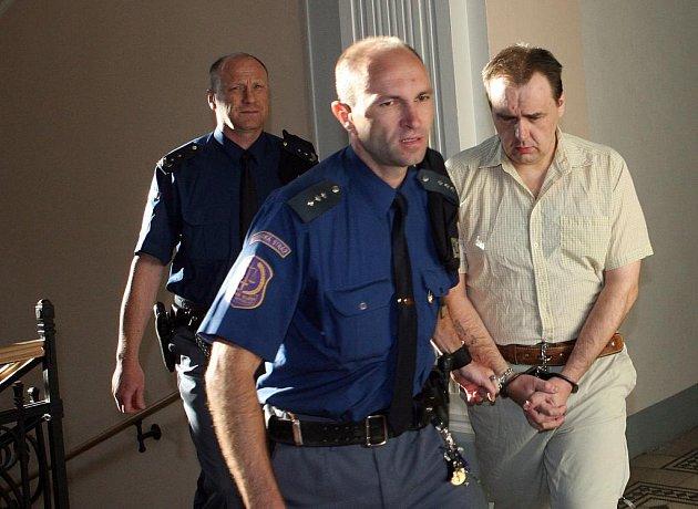 Romana Sklenáře vede vězeňská stráž k hlavnímu líčení.
