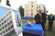 Vladislav Smrčka, primář dětského oddělení českobudějovické nemocnice, symbolicky poklepává na základní kámen nového pavilonu. Zatímco za zády má současnou budovu, v popředí je vidět již animace budoucího pavilonu.