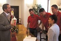 Štěpán Smrčka (mezi druhým zleva masérem Hochem a smečařem Zachem – vpravo) se zapisuje se svými spoluhráči do pamětní knihy města při návštěvě u primátora Juraje Thomy (vlevo).