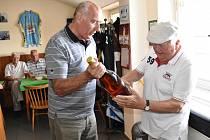 Petr Hudler předává organizátoru setkání Janu Pouzarovi jako dárek maxiláhev jindřichohradeckého rumu.