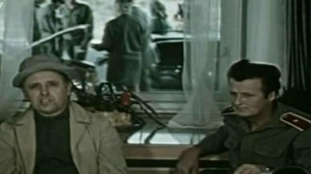 Muž z Londýna. Na snímku je vyslýchán herec Václav Babka (Fifka), za ním průhledem v okně pracují celníci