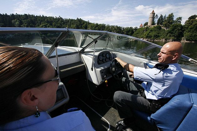 Policista Tomáš Souhrada za řízením motorového člunu projíždí pod Zvíkovem.