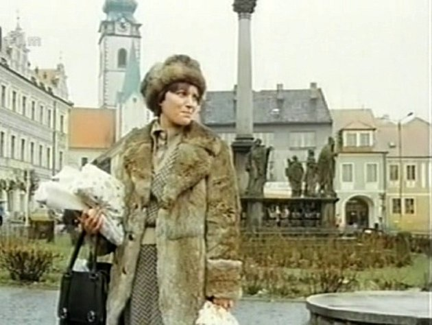 Písecké Alšovo náměstí smorovým sousoším a vychovatelkou. Vzadu se tyčí věž děkanského kostela Narození Panny Marie.