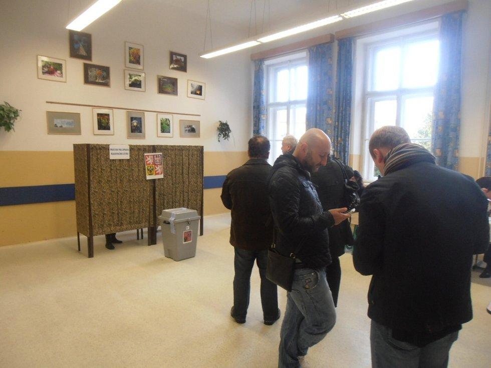 V budově gymnázia v českobudějovické České ulici se voliči míjejí s účastníky páteční oslavy 110. výročí otevření budovy gymnázia.