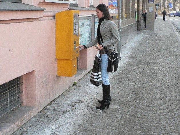 Rozbitá dlažba na zastávce MHD v ulici Na Sadech nutí zájemce o koupi jízdenky k hodně opatrnému našlapování.