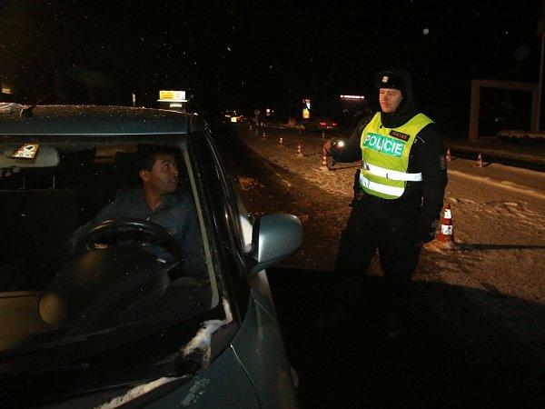 Policisté, kteří kontrolují auta na hraničním přechodu Dolní Dvořiště, zažívají nyní mrazivé noci, kdy teplota padá kminus deseti a ještě níž. Nejhorší pro ně je ledový vítr. Na snímku zneděle 17.ledna Miroslav Rojdl.