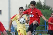 Třeboňský Kupka (vpravo) v zápase posledního kola divize s Dobříší (1:2) odkopává míč před  hostujícím Peckou.