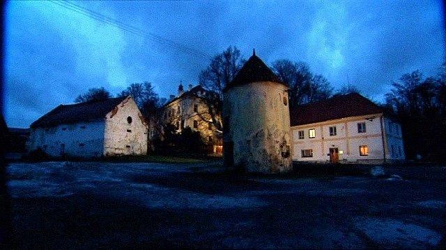 Noční záběr na němčický zámek s budovami, vpravo sídlo komunity, vepředu stojí rotundovitá šatlava.