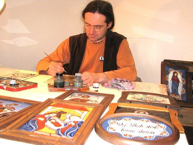 Jiří Honiss, povoláním výpravčí, mění ve svém volnu plácačku za štětec a maluje na sklo obrázky svatých.