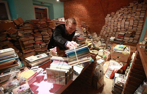 Jakub Albín, jeden ze spolupořadatelů festivalu Literatura žije, ukazuje vLiterární kavárně Měsíc ve dne, kolik knih jim přinesli lidé díky sbírce do pouliční veřejné knihovny vČeských Budějovicích.
