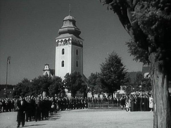 Sever náměstí spůvodní zelení a lípou Svobody. Film ukazuje  původní lampu. Dnes je náměstí po rekonstrukci (mj. nové stromy, kašna je posunuta pod lípu).