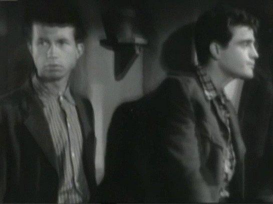Záběr zfilmu Všude žijí lidé. František Kohout zChyšek si zahrál vkomparzu. Vtomto záběru stojí na družstevní schůzi sJanem Třískou.