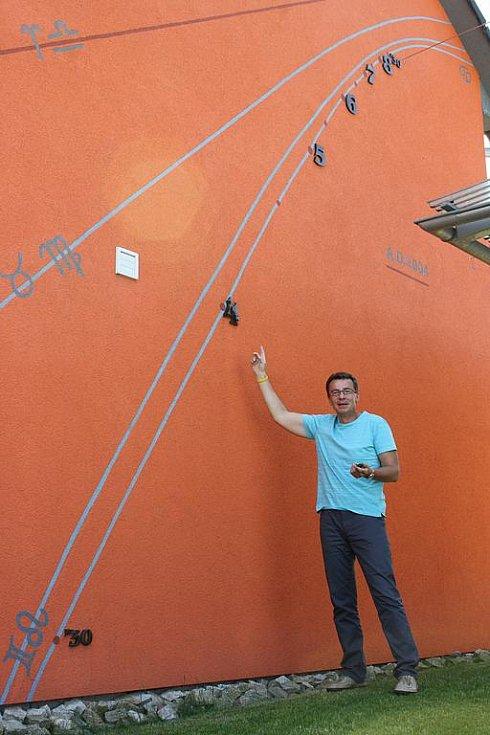 Jan Zeman ukazuje sluneční hodiny na svém domě v Boršově nad Vltavou. Ty si vytvořil v roce 2004 a musel přitom strávit na žebříku u stěny celkem čtyřicet hodin.