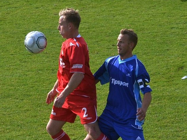 Milan Nousek v zápase krajského přeboru mezi Pískem B a Soběslaví bojuje s hostujícím Jiřím Richterem. Fotbalové soutěže v kraji o víkendu pokračují.