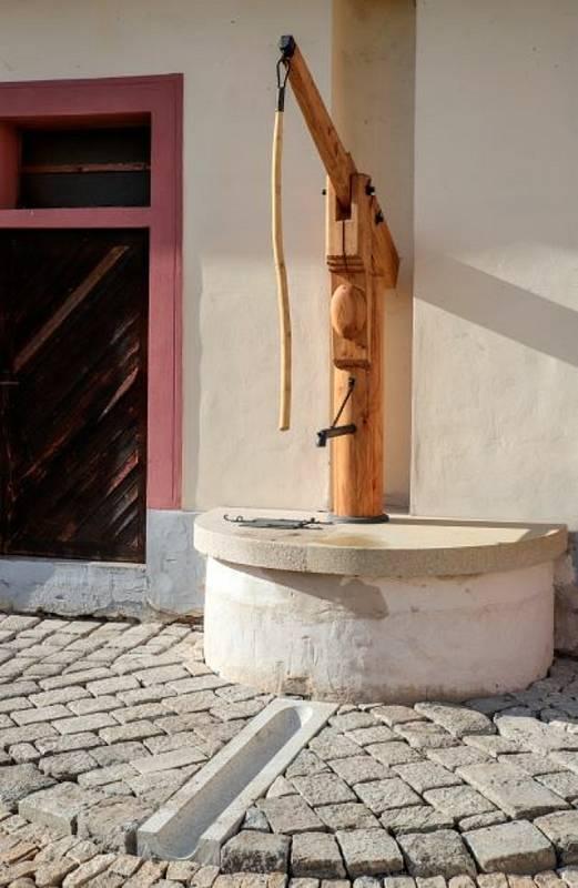 Replika dobové dřevěné pumpy na zámeckém nádvoří.