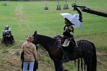 Herec Pavel Kříž se schovává pod deštníkem, na ním vykukuje rameno kamery.