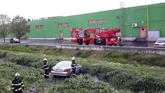 Jeřáb si s autem uvízlým v betonové stoce poradil.